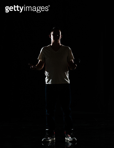 Full length / one man only / one person / front view of 20-29 years old adult handsome people caucasian male / young men singer / musician standing / dancing in front of black background wearing canvas shoe / jeans / pants / t-shirt / shirt