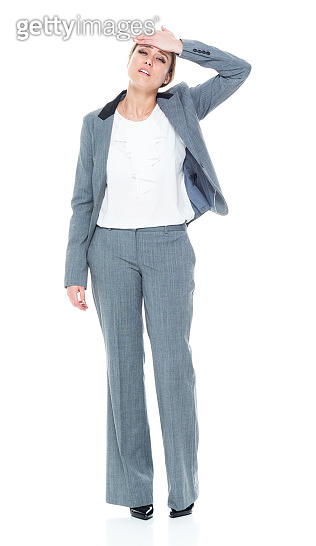 One person / full length / front view of 20-29 years old adult beautiful caucasian female / young women businesswoman / business person standing wearing a suit who is headache / emotional stress / dizzy / in pain / distraught