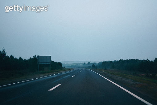 Empty highway in early foggy morning
