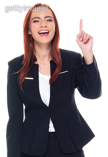 One person / waist up / portrait of 20-29 years old adult beautiful redhead / long hair caucasian female / young women businesswoman / business person standing wearing businesswear / a suit and showing index finger giving number one finger sign