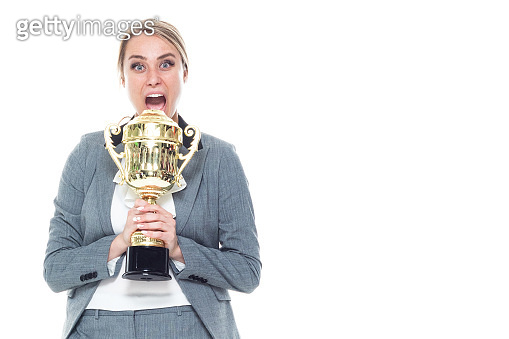 One person / front view / waist up of 20-29 years old adult beautiful caucasian female / young women businesswoman / business person standing wearing a suit who is smiling / happy / cheerful / successful and winning / showing award