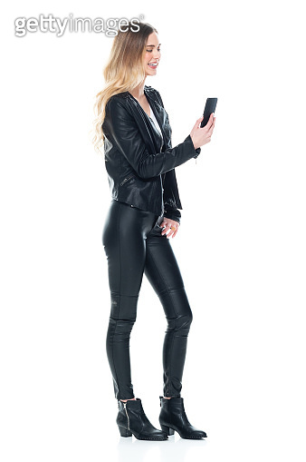 Full length / side view / profile view / one person of 20-29 years old adult beautiful blond hair / long hair caucasian / generation z female / young women standing wearing leather jacket / pants / boot / t-shirt / shirt and holding mobile phone