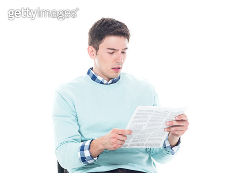 Handsome young man sitting and reading a document in a serious manner