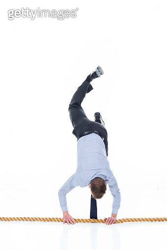 Full length / one person of 20-29 years old adult handsome people caucasian male / young men business person / businessman / manager agility / walking / handstand / exercising / upside down in front of white background wearing necktie who is courage