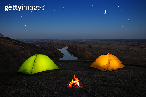 Orange and green tent by the river at night
