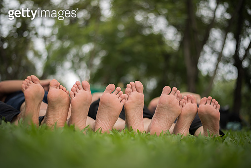 Close up of family feet togetherness on green field.