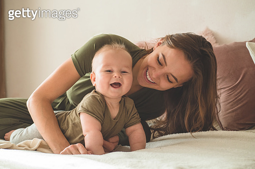 Home portrait of a baby boy with mother on the bed. Mom holding and kissing her child.