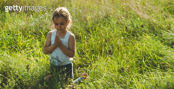Little girl closed her eyes, praying outdoors, Hands folded in prayer concept for faith, spirituality and religion. Peace, hope, dreams concept.