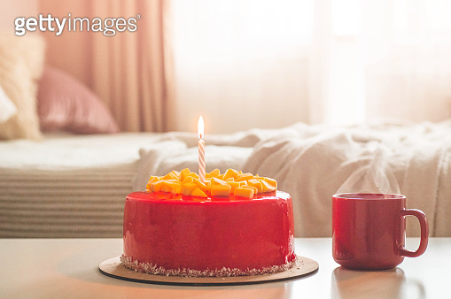 Birthday cake with one candle and red frosting. National bakery. Round cake with mango