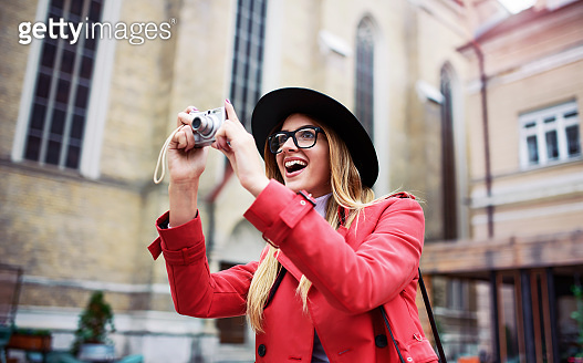Happy woman on vacation making a photos with camera. Concept of tourism