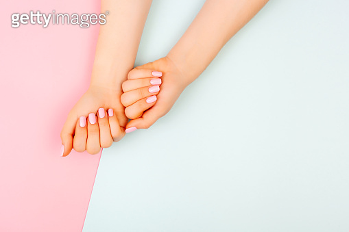 Hands of a beautiful woman on a colorful background.