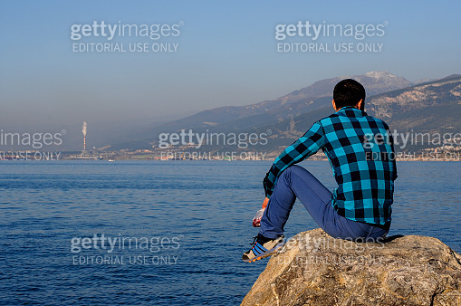 young man sits on the shore of the blue sea against the background of the mountains