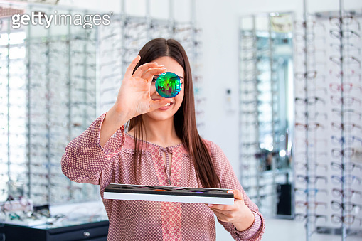 Attractive young female doctor in ophthalmology clinic showing different polarized lens