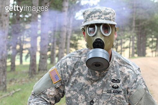 Army soldier wearing gas mask in nature