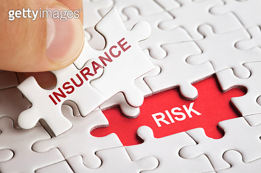 Hand holding piece of puzzle with word INSURANCE RISK.