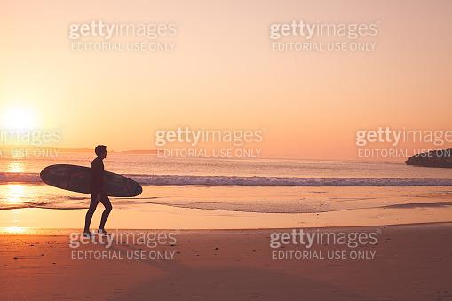 Peniche - Portugal - 26 September 2018 - Surfer running on the beach at sunrise