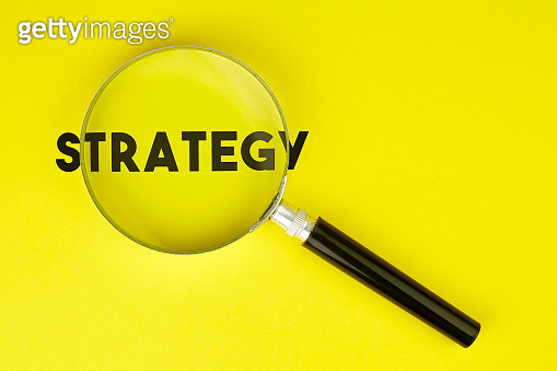 Magnifier And Strategy Text On Yellow Background Stock Photo