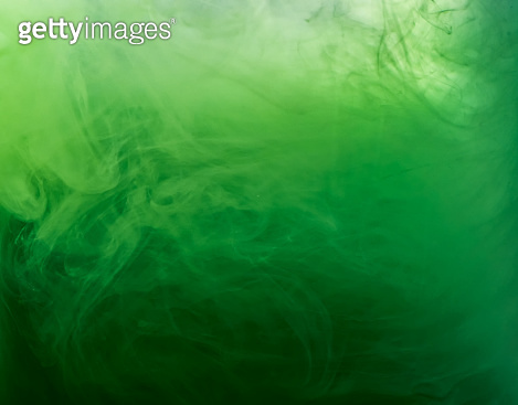 Abstract green smoke under water, blurred background. Close up view. Paint dissolving into water, abstract background. Acrylic clouds in liquid. Background for abstract wallpapers and banners.