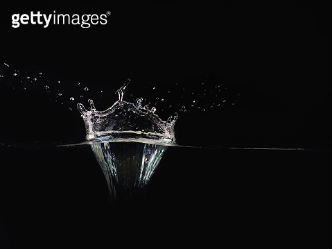 Splash of water isolated on black background, close up view. Drop of water makes splash on surface, background for overlays design, screen blending mode layer.