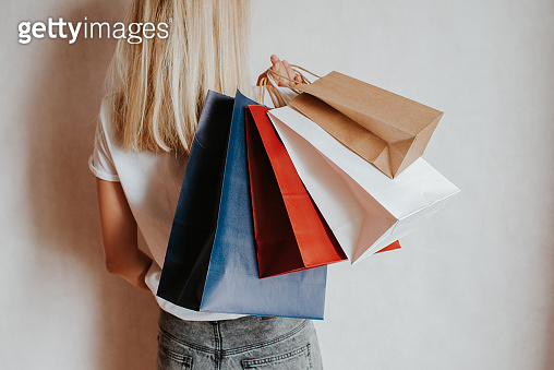 Happy woman holding in hand shopping package. Paper bag. Sale in store. Beautiful young girl in fashion shop. Customer buy present. Black friday sale. Holiday special offer, discount. Female in market