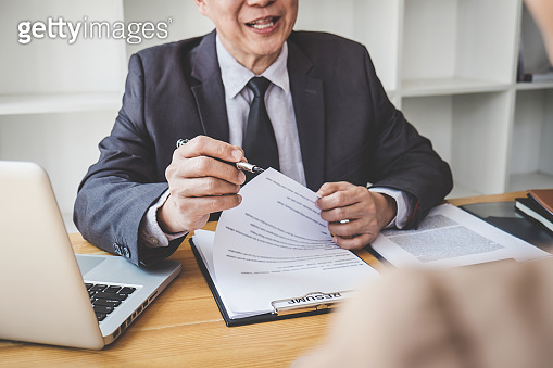 Interviewer or Board reading a resume during a job interview, Employer interviewing a young female job seeker for recruitment talking in modern office, employment and recruitment concept