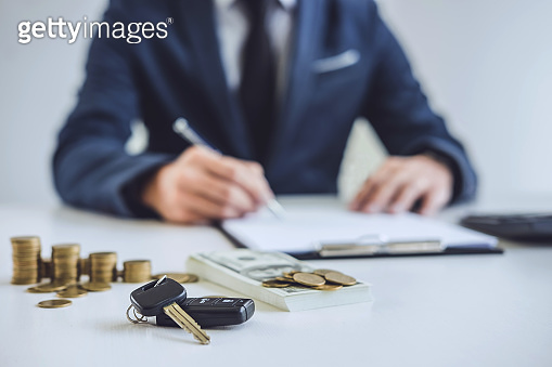 Salesman analyzing cost of buying new car and insurance document, Writing signature on contract to selling to customer