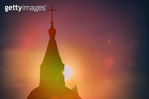 Misty beautiful sunset light of the sun illuminates catholic church. Rays of light against the black sky. Religious symbol - catholic cross on summer evening. Dark cloudy sky waiting for the night.