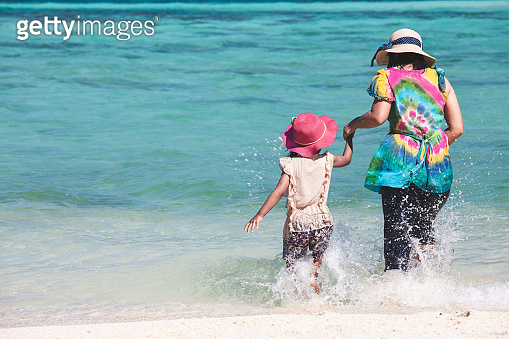 Young asian mother and cute little daughter playing water together in the beautiful sea