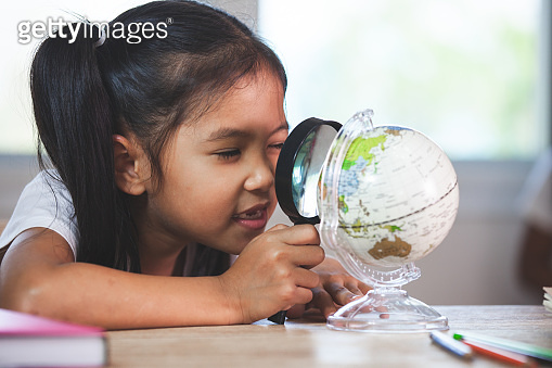 Cute asian child girl use magnifier to look and study at the globe