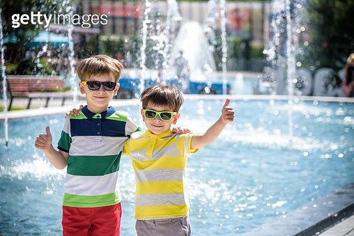 Group of happy children playing outdoors near pool or fountain. Kids embrace show thumb up in park during summer vacation. Dressed in colorful t-shirts and shorts with sunglasses. Summer holiday concept