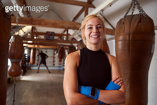 Portrait Of Smiling Female Boxer With Protective Wraps On Hands Training In Gym