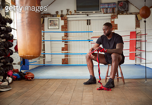 Male Boxer Training In Gym Sitting Next To Boxing Ring Putting Wraps On Hands