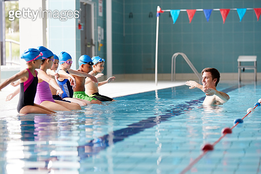 Male Coach In Water Gives Children Instructions In Swimming Lesson As They Sit On Edge Of Pool