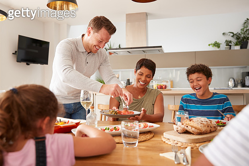 Father Serving As Multi-Generation Mixed Race Family Eat Meal Around Table At Home Together