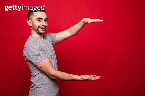 Young man holding two hands in front of him and shows the size on red isolated background in studio. human emotion, facial expression, feeling attitude