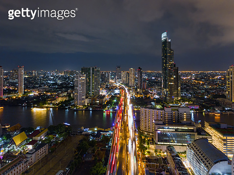 Aerial view of Taksin Bridge with Chao Phraya River, Bangkok Downtown. Thailand. Financial district and business centers in smart urban city. Skyscraper and high-rise buildings at night.