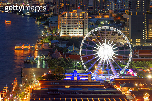 Aerial view of the ferris wheel, Asiatique The Riverfront, near Chao Phraya River with skyscraper buildings in Bangkok Downtown at night, urban city, Thailand.