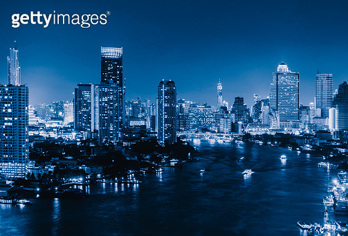 Aerial view of boats and Taksin Bridge with Chao Phraya River, Bangkok Downtown. Thailand. Financial district and business centers in smart urban city. Skyscraper and high-rise buildings at night.
