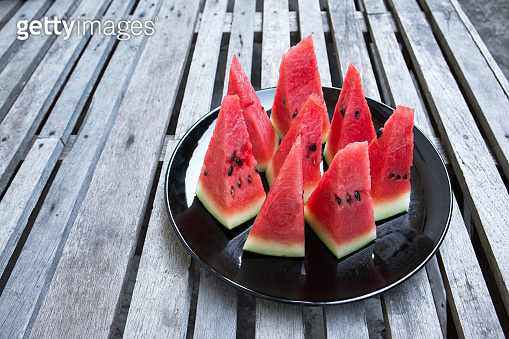 Slice watermelon in plate on wood table background. Pieces of watermelon in black dish on wooden table