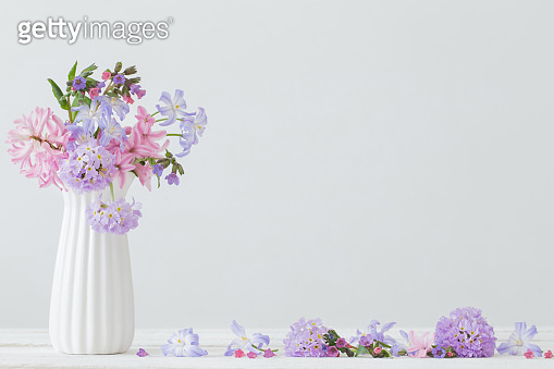 blue and pink flowers in vase on white table