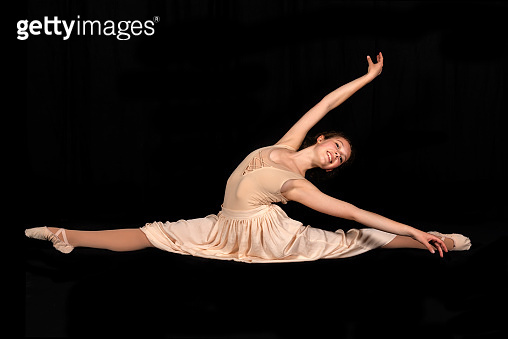 Young ballerina is dancing on black background