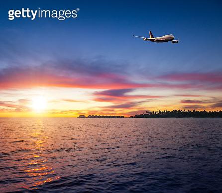 Beautiful sunset on Maldives resort with airplane