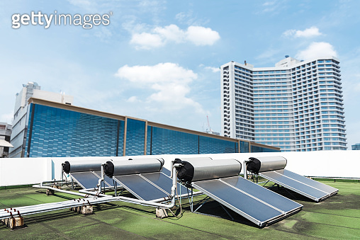Ecological energy renewable solar panels on the roof in the city with blue sky. Free copy space for text.