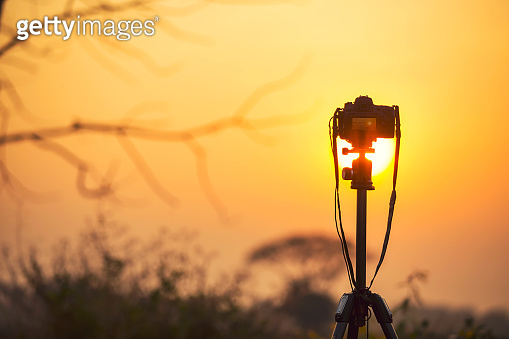 DSLR camera mounted on a tripod with sunset sky. Photographer and photography concept.