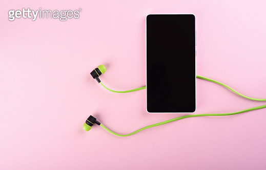 Smartphone and green headphones isolated on pink background.