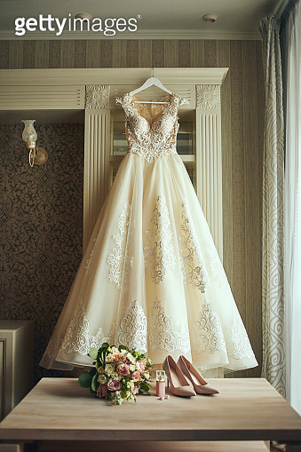 beautiful wedding dress hanging in the room, woman getting ready before  ceremony