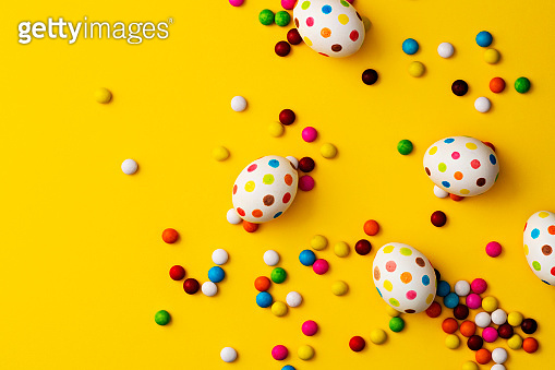 Spotty painted colourful easter eggs  and colourful chocolate beans on yellow background
