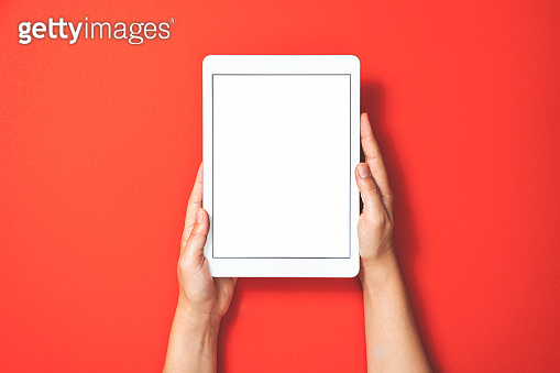 Hands holding digital tablet on red background