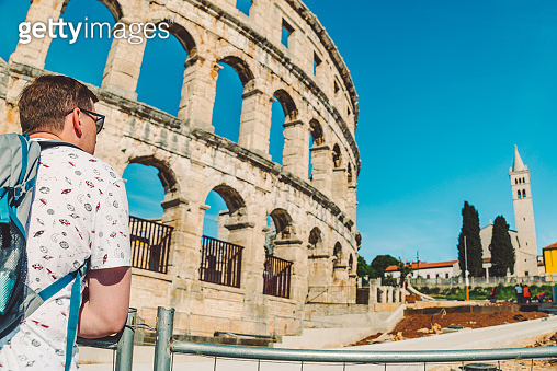 young man tourist standing near old roman coliseum in pula croatia. tourism concept