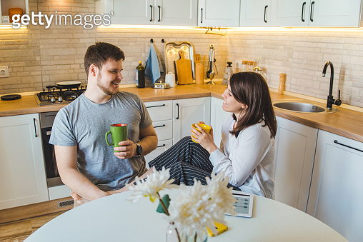 couple talking at the kitchen in the morning drinking tea